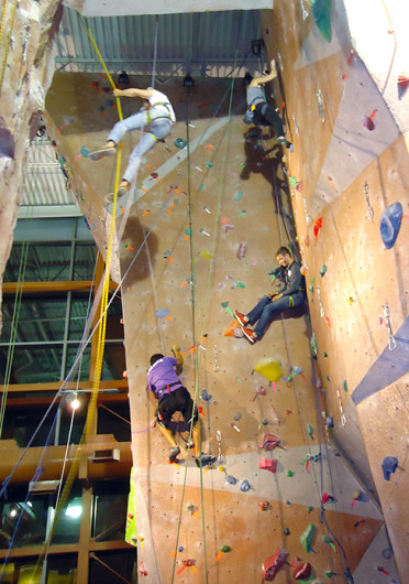 Students Amit Raghvanshi (bottom left) and Krista Bryson (top right) race past zombies on the climbing wall for the Outdoor Adventure Center's Zombie Climbing Competition on Oct. 13.  Credit: Nick Roll / Lantern reporter