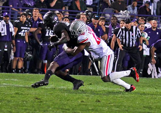 Junior cornerback Doran Grant (12) tackles a receiver during a game against Northwestern Oct. 5 at Ryan Field. OSU won, 40-30. Credit: Shelby Lum / Photo editor