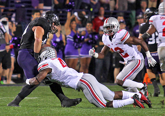 Redshirt-senior safety C.J. Barnett (4) tackles an opponent during a game against Northwestern Oct. 5 at Ryan Field. OSU won, 40-30. Credit: Shelby Lum / Photo editor