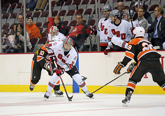 Junior forward Ryan Dzingel (18) splits two defenseman during a game against Bowling Green Oct. 29 at the Schottenstein Center. OSU won, 5-3. Credit: Shelby Lum / Photo editor