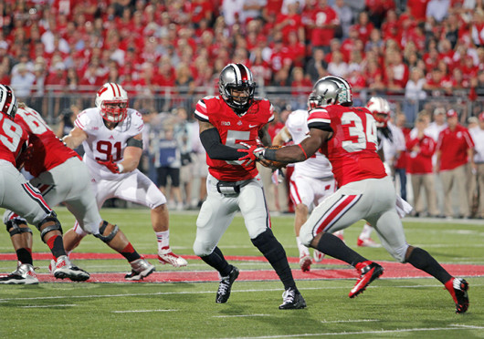 Junior quarterback Braxton Miller (5) hands the ball off to senior running back Carlos Hyde (34) during a game against Wisconsin Sept. 27 at Ohio Stadium. OSU won, 31-24. Credit: Ritika Shah / Asst. photo editor