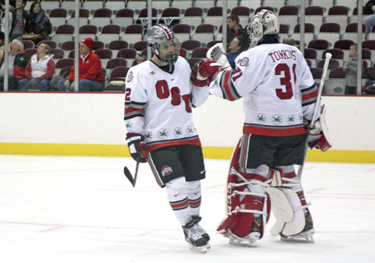 Freshman goalie Matt Tomkins (31) and senior forward Travis Statchuk (12) celebrate during a game against Robert Morris Oct. 25 at the Schottenstein Center. OSU won, 5-3. Credit: Julia Hider / Lantern photographer