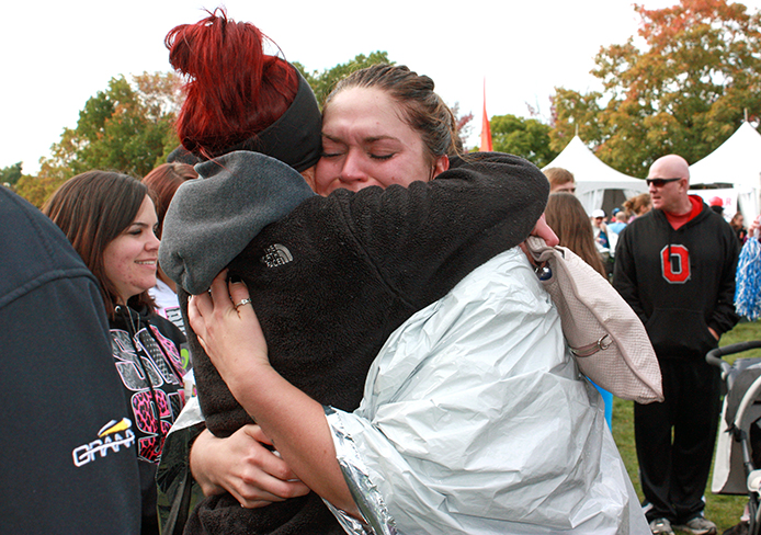Lauren Simon sheds a tear while hugging friends and family after completing the Columbus half marathon Oct. 20. More than 15,000 people completed the race, which started and ended in downtown Columbus.