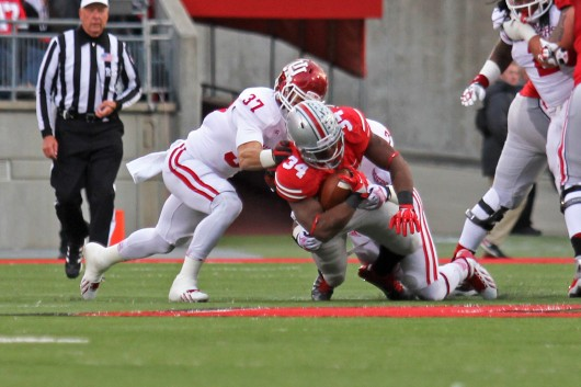 Senior running back Carlos Hyde (34) pushes through Indiana defenders for his 1,000th rushing yard of the season. Hyde became the first running back under coach Urban Meyer to eclipse the 1,000-yard mark. Credit: Shelby Lum / Photo editor