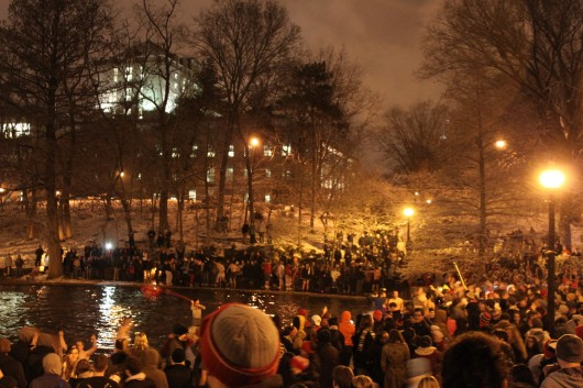Fans stand around Mirror Lake while some jump in despite university efforts to control the event.  Credit: Ryan Robey / For The Lantern