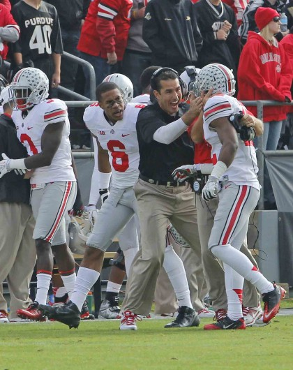 Defensive coordinator and linebackers coach Luke Fickell celebrates with junior cornerback Doran Grant (12) following an interception during a game against Purdue Nov. 2, 2013 at Ross-Ade Stadium. OSU won, 56-0. Credit: Lantern File Photo