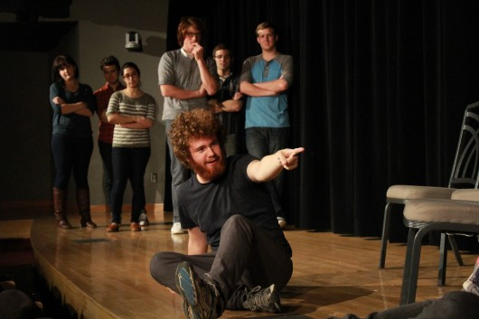 Fourth-year in biomedical engineering, Stephen Doughten, sits on stage as other Fishbowl Improv members look on at the Bellwether Improv Festival Nov. 8.
