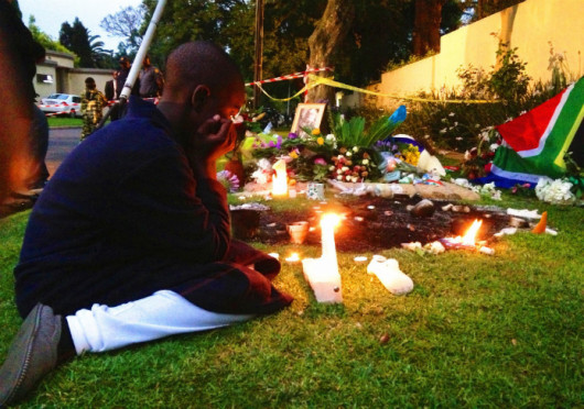 A boy lights a candle outside the house of former South African President Mandela, Dec. 6, 2013 in Johannesburg, South Africa. The South African anti-apartheid hero died peacefully at home at the age of 95 on Thursday, Dec. 5, after months fighting a lung infection.