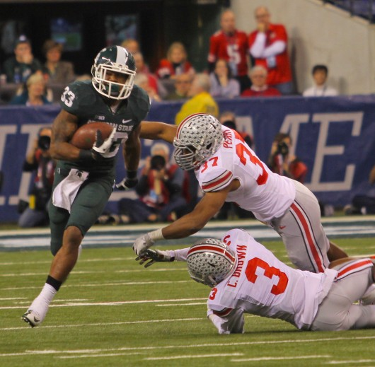 Redshirt-senior safety Corey Brown (3) and sophomore linebacker Joshua Perry (37) attempt to make a tackle during the Big Ten Championship Game Dec. 7 in Indianapolis. OSU lost, 34-24, to Michigan State. Credit: Shelby Lum / Photo editor