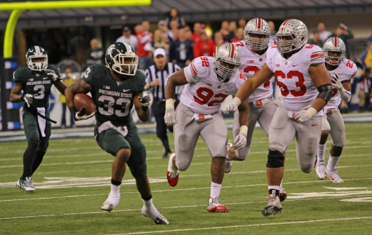 Then-junior defensive lineman Michael Bennett (63) chases a Michigan State player during the Big Ten Championship Game against the Spartans on Dec. 7, 2013, at Lucas Oil Stadium in Indianapolis. OSU lost, 34-24. Credit: Lantern file photo