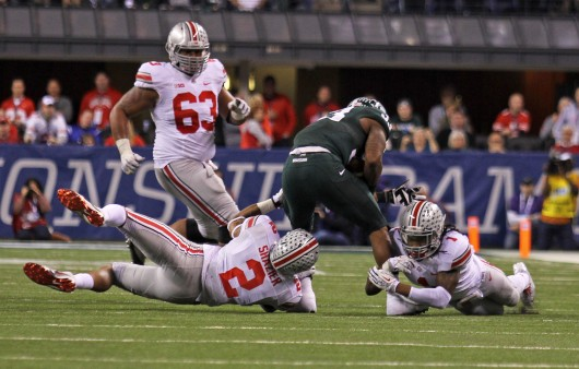 Junior linebacker Ryan Shazier (2) and redshirt-junior cornerback Bradley Roby (1) make a tackle during the Big Ten Championship Game Dec. 7 in Indianapolis. OSU lost to Michigan State, 34-24. Credit: Shelby Lum / Photo editor