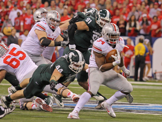 Senior running back Carlos Hyde (34) breaks through the line on a run during the Big Ten Championship Game Dec. 7 in Indianapolis. OSU lost to Michigan State, 34-24. Credit: Shelby Lum / Photo editor