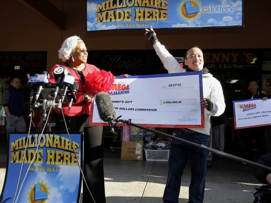 Store owner Thuy Nguyen (right) accepts a check for $1 million from Mona Sanders of the California Lottery for selling a winning Mega Millions lottery ticket in San Jose, Calif., Dec. 18. Credit: Courtesy of MCT