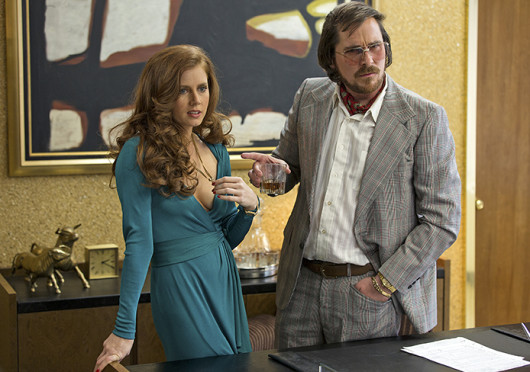 Sydney Prosser (Amy Adams, left) and Irving Rosenfeld (Christian Bale) attempt to scam an undercover agent in Columbia Picutres' 'American Hustle.' The film is set to release in theaters Dec. 18.  Credit: Courtesy of Francois Duhamel / Annapurna Productions