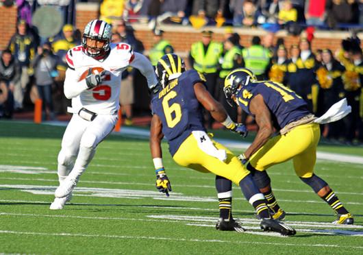 Junior quarterback Braxton Miller (5) attempts to avoid defenders during The Game Nov. 30 at Michigan Stadium. OSU won, 42-41. Credit: Shelby Lum / Photo editor