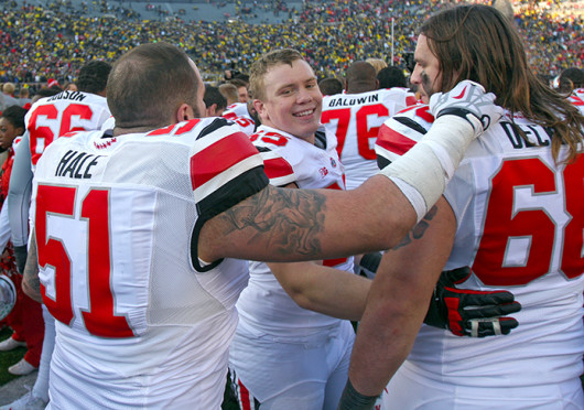 Redshirt-freshman right guard Pat Elflein (65) celebrates with junior defensive lineman Joel Hale (51) and sophomore right tackle Taylor Decker (68) after a game against Michigan Nov. 30 at Michigan Stadium. OSU won, 42-41. Credit: Shelby Lum / Photo editor