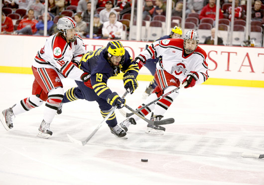 Freshman defenseman Drew Brevig (4) and junior forward Tanner Fritz (16) flank an opposing player during a game against Michigan Dec. 2 at the Schottenstein Center. OSU lost, 5-4. Credit: Kelly Roderick / For The Lantern