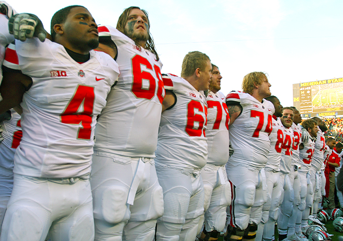 Redshirt-senior safety C.J. Barnett (4) stands with his teammates at the end of the game against Michigan Nov. 30 during 'Carmen Ohio.' OSU won, 42-41. Credit: Shelby Lum / Photo editor