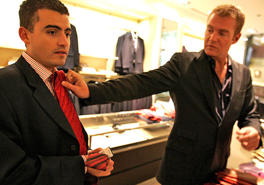 Fernando Beteta (left) tries a tie with the help of sales associate Michael Andersen of the Hugo Boss store in Chicago.