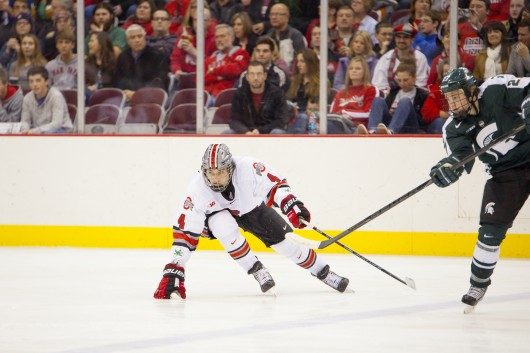 Freshman defenseman Drew Brevig (4) attempts to regain his balance during a game against Michigan State Jan. 11 at the Schottenstein Center. The teams tied, 1-1. Credit: Kelly Roderick / For The Lantern