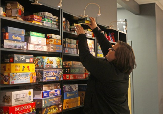 Melissa Vargo searches through board games at Kingmakers, which carries about 230 titles. The board game parlour is located at 17 Buttles Ave.  Credit: Shelby Lum / Photo editor
