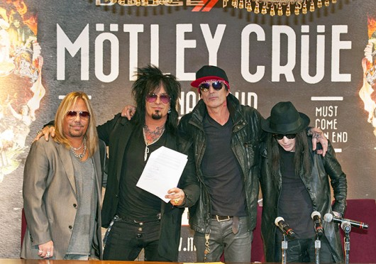 Motley Crue band members Vince Neil, Nikki Sixx, Tommy Lee and Mick Mars stand together with their signed 'Cessation of Touring' document Jan. 28.  Credit: Courtesy of MCT
