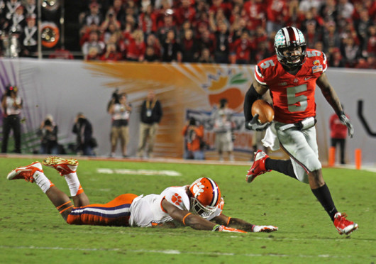 Junior quarterback Braxton Miller (5) runs away from a Clemson defender during the 2014 Discover Orange Bowl Jan. 3 at Sun Life Stadium. OSU lost, 40-35. Credit: Shelby Lum / Photo editor