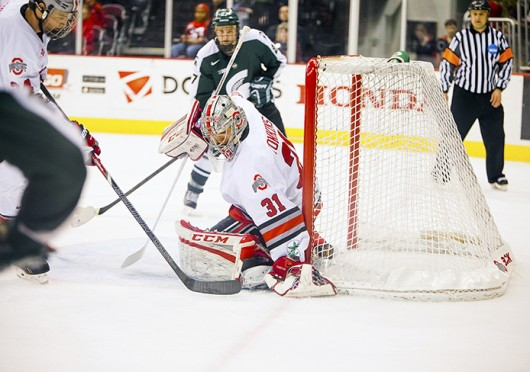 Freshman goalkeeper Matt Tomkins (31) saves the puck during a game against Michigan State Jan. 11 at the Schottenstein Center. The teams tied, 1-1. Credit: Kelly Roderick / For The Lantern