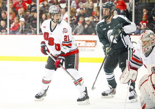 Sophomore defenseman Sam Jardine (21) marks his man during a game against Michigan State Jan. 11 at the Schottenstein Center. The teams tied, 1-1. Credit: Kelly Roderick / For The Lantern