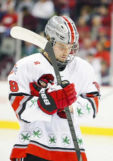 Senior forward Alex Szczechura takes off his gloves during a game against Michigan State Jan. 11 at the Schottenstein Center. The teams tied, 1-1. Credit: Kelly Roderick / For The Lantern