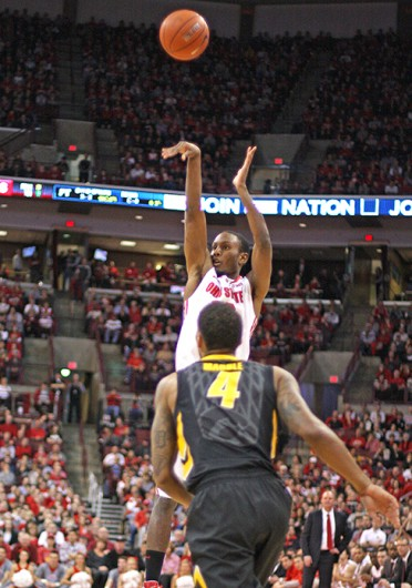 Junior forward Sam Thompson (12) takes a 3-pointer during a game against Iowa Jan. 12 at the Schottenstein Center. OSU lost, 84-74. Credit: Shelby Lum / Photo editor