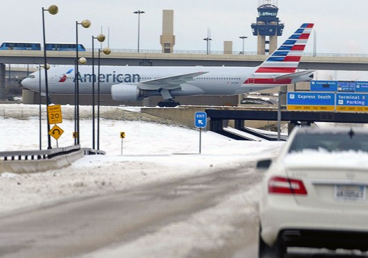 An American Airlines jet crosses International Parkway as motorists travel slowly at Dallas/Fort Worth International Airport Dec. 6.