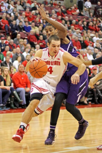 Senior guard Aaron Craft (4) drives past an opponent during a game against Northwestern Feb. 19 at the Schottenstein Center. OSU won, 76-60. Credit: Shelby Lum / Photo editor