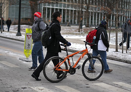 A man walks a bike across 18th Avenue. OSU students living on 4th and Summit streets could soon see designated biking lanes on their roads. Credit: Shelby Lum / Photo editor