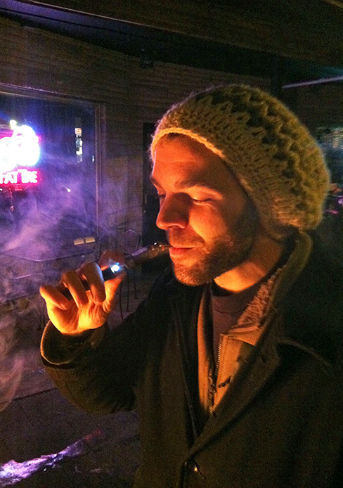 Columbus resident Phil Risko takes a drag from his e-cigarette while listening to local music at the Woodlands Tavern Jan. 30. Risko said bought an e-cigarette to quit smoking cigarettes. Credit: Jonathan McAllister / Lantern photographer
