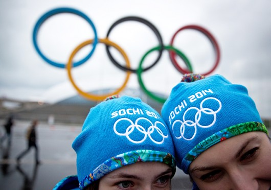 People pose for a picture under the Olympic rings at the Olympic Park in Sochi, Russia, Jan. 31.  Credit: Courtesy of MCT