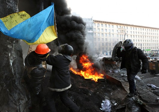 Ukrainian protesters raise a national flag over a barricade on Grushevsky Street in downtown Kiev during clashes with riot police Jan. 25. Credit: Courtesy of MCT