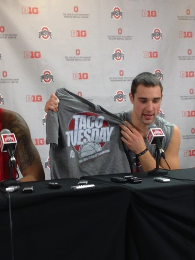 Senior guard Aaron Craft holds up a Taco Tuesday T-shirt Monday during interviews at the Schottenstein Center. The shirts will cost $20 and will be sold in the southwest entrance of the Schottenstein Center as well as the team shop inside, and proceeds will benefit OSU LiFE Sports. Credit: Eric Seger / Sports editor