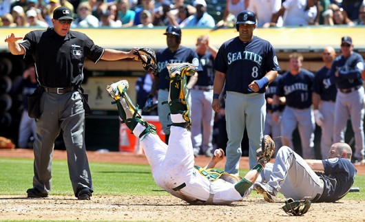 Seattle Mariners outfielder Dustin Ackley (right) is called safe at home after a collision with Oakland Athletics catcher Stephen Vogt (middle) Aug. 21 at O.co Coliseum. Seattle won, 5-3. Courtesy of MCT