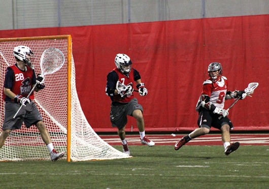 Freshman attackman JT Blublaugh (9) looks for an open teammate during a game against Robert Morris Feb. 1 at the Woody Hayes Athletic Center. OSU won, 11-7. Credit: Ryan Robey / For The Lantern