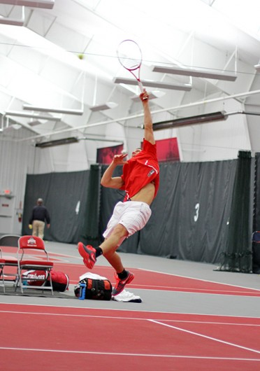 Redshirt junior Kevin Metka reaches up for an overhead to win the point in a doubles match against Xavier. OSU won, 7-0, Jan. 22 at the Varsity Tennis Courts. Credit: Shelby Lum / Photo editor