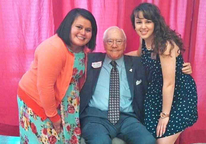 Haley de Leon (left) and Michele Theodore (right), members of Mount Leadership Society, pose for a picture with John Mount at an event for the organization April 7.