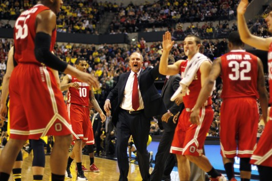 Coach Thad Matta (center) talks to his players during a game against Michigan March 15 at Bankers Life Fieldhouse. OSU lost, 72-69. Credit: Shelby Lum / Photo editor
