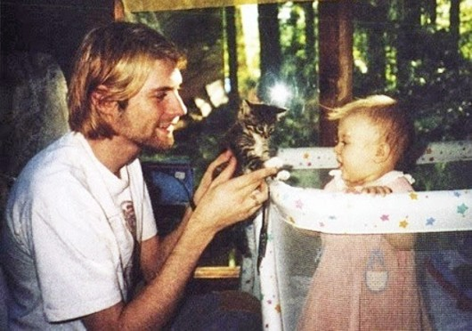 Kurt Cobain (left), the former frontman of Nirvana, holds up a kitten to his daughter, Frances Bean Cobain.