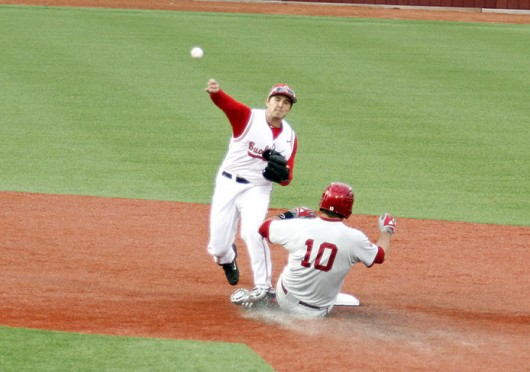 Sophomore infielder Troy Kuhn (left) throws the ball to 1st base during a game against Indiana March 28 at Bill Davis Stadium. OSU lost, 6-4. Credit: Nick Deibel / Lantern reporter