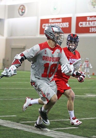 Then-senior attackman Logan Schuss (18) advances the ball during a game against Detroit Feb. 9 at the Woody Hayes Athletic Center. OSU won, 14-8. Credit: Shelby Lum / Photo editor
