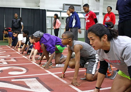 OSU LiFESports counselor Tarkington Newman (bottom right) gets set to race kids who participated in the track & field clinic held March 29 at French Field House. Credit: Matt Homan / Lantern reporter