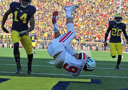 Then-junior wide receiver Devin Smith (9) falls to the ground after catching a touchdown pass during a game against Michigan Nov. 30 at Michigan Stadium. OSU won, 42-41. Credit: Shelby Lum / Photo editor