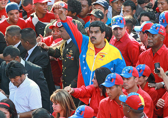 Then-Vice President Nicolas Maduro of Venezuela greets the crowd as thousands of supporters of then-President Hugo Chavez pay respects as his funeral procession travels through Caracas, Venezuela, March 6, 2013.