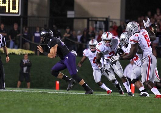Then-senior Northwestern quarterback Kain Colter (2) avoids OSU defenders during a game Oct. 5 at Ryan Field. OSU won, 40-30. Credit: Shelby Lum / Photo editor